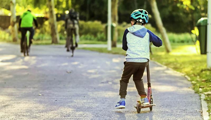 Kleiner Junge fährt mit Scooter Roller auf Straße